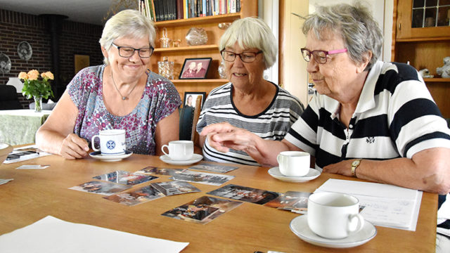 Snakken går livligt hen over kaffebordet hos Erna Kristensen, mens Tove Pedersen (t.v.), Erna Kristensen og Grethe Moesner ser på billeder fra 40 år med Hjerting Folkedansere.