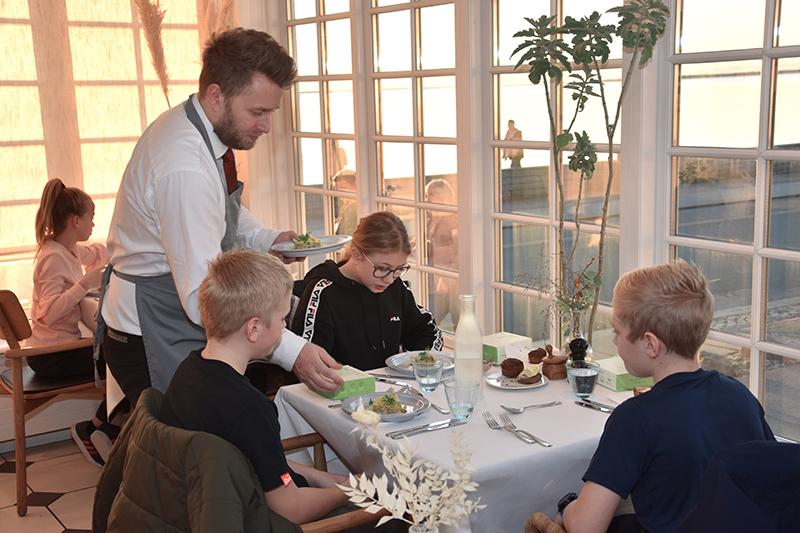 Tjener Mads Kisum serverer for et bord med glade gæster.